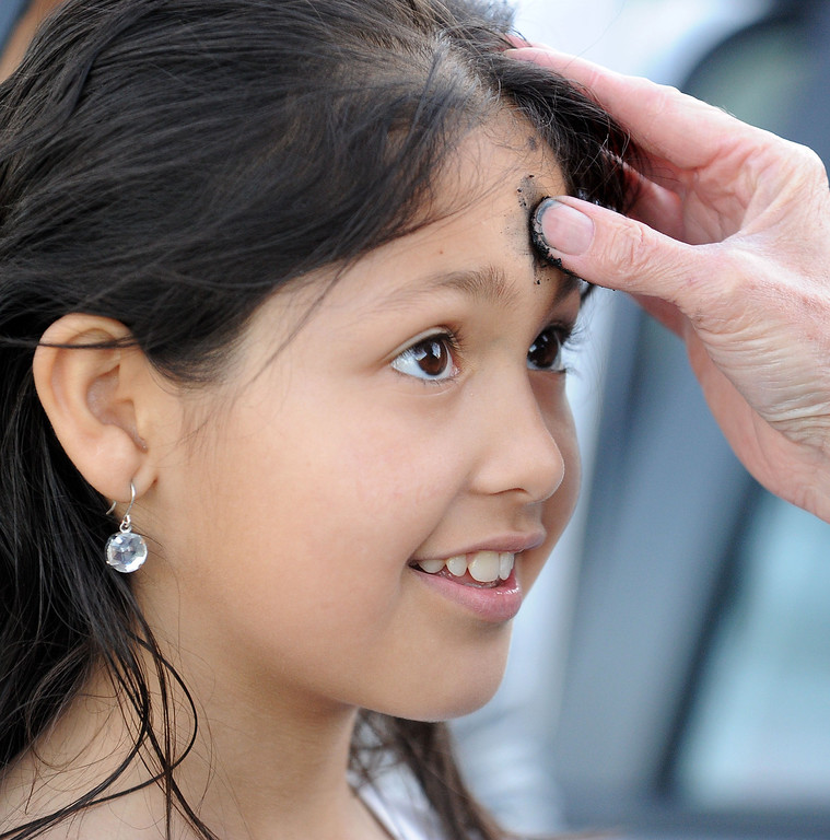 . Lesly Gonzalez, 8, of Antioch, gets some ashes from The Rev. Christy Parks-Ramage, with the First Congregational Church of Antioch, during the drive-by prayers and the imposition of ashes for Ash Wednesday held in Pittsburg, Calif., on Wednesday, Feb. 13, 2013. The drive-through Ash Wednesday was held by the East County Shared Ministry. (Doug Duran/Staff)