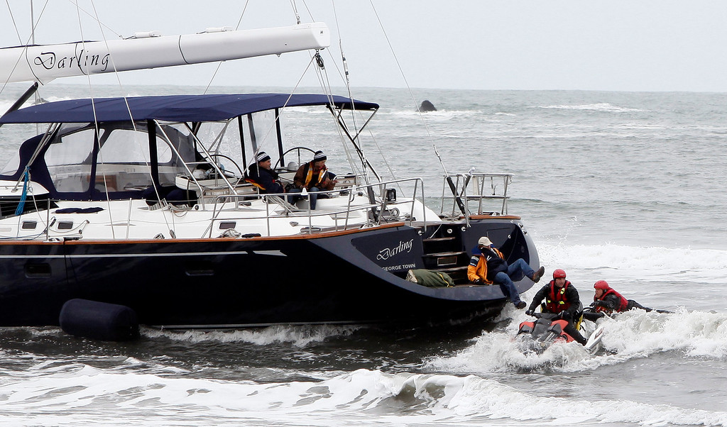 . Rescuers attempt to grab a man off the back of the 82-foot-long sailboat, the Darling, stuck in the surf off Linda Mar Beach in Pacifica, Calif., Monday morning March 4, 2013. The boat had been reported stolen from a Sausalito marina earlier. The three people aboard were all rescued and arrested. (Karl Mondon Photo)