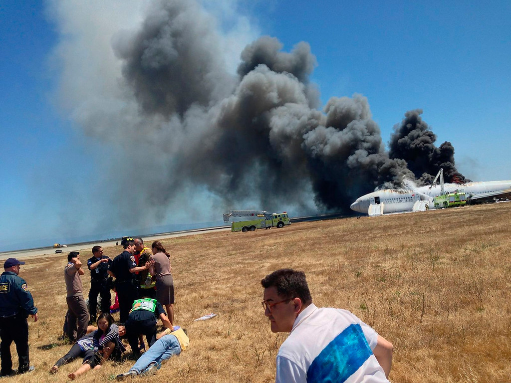 . First responders tend to Asiana Airlines flight attendants and rescued passengers as they gather near the runway after flight 214 crash landed at San Francisco International Airport on July 6, 2013. (Eugene Anthony Rah via Reuters)i