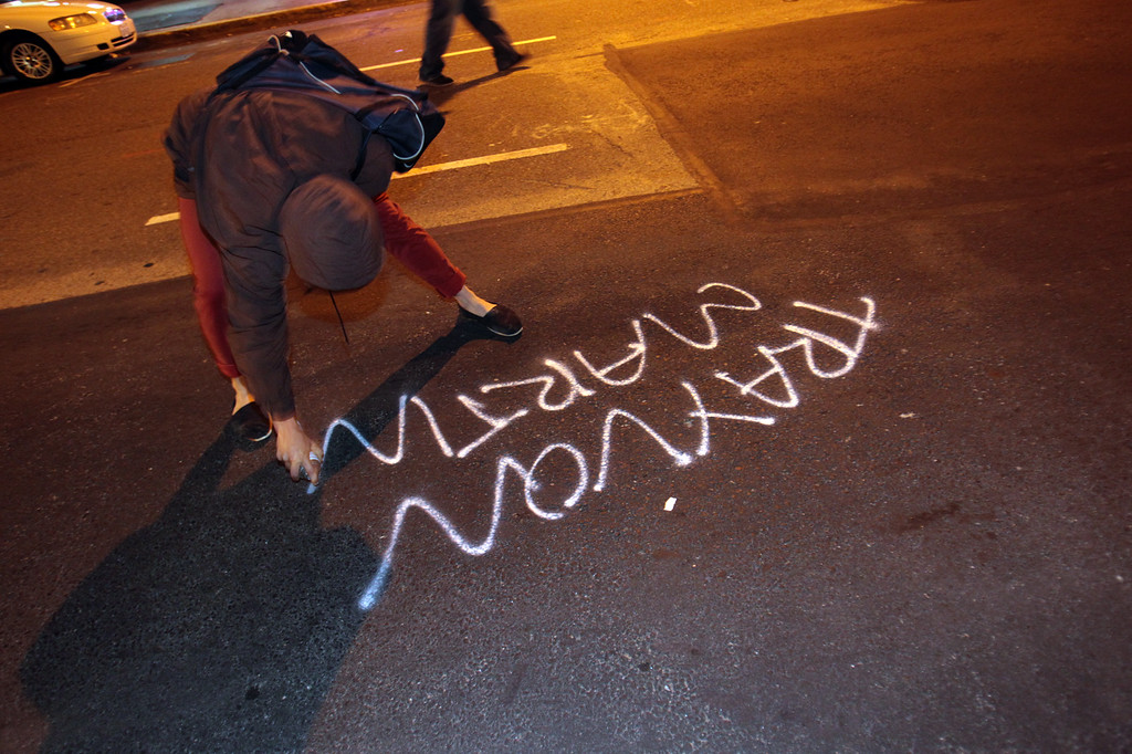 . A woman sprays the name Trayvon Martin in paint along Franklin Street during a protest march in Oakland, Calif., on Saturday, July 13, 2013. Protesters marched through the city with some in the group smashing windows, spraying graffiti and setting fires after learning that George Zimmerman had been found not guilty in the shooting death of Trayvon Martin. (Anda Chu/Bay Area News Group)