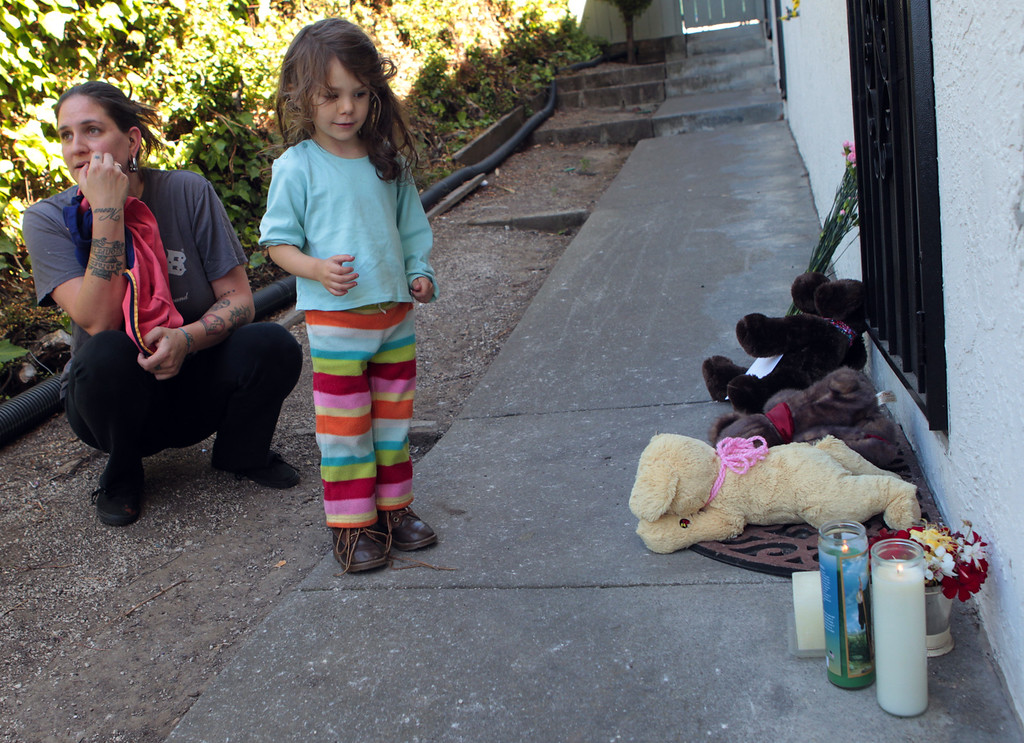 . Eleni, who declined to give her last name, and daughter Ember, 2, of Oakland, pay their respects outside the home where an 8-year-old girl was killed in a shooting that also injured two other children and an adult along Wilson Avenue in Oakland, Calif., on Thursday, July 18, 2013. (Anda Chu/Bay Area News Group)