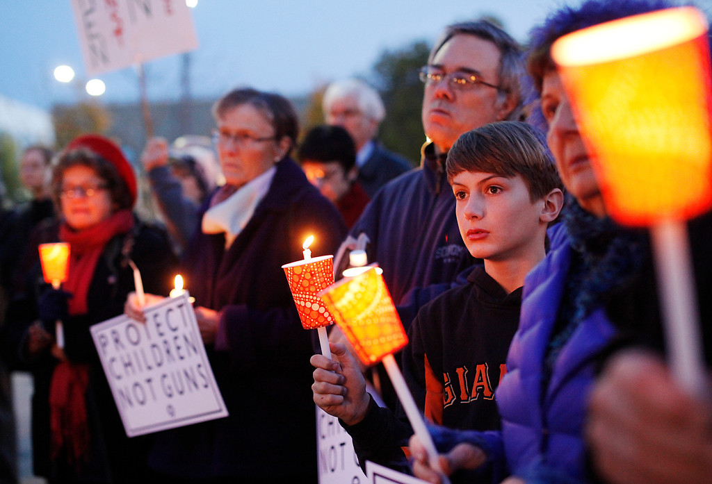 """. Harrison Frahn, 11, second from right, listens to a speech during a candlelight vigil in Lytton Plaza in downtown Palo Alto supporting an end to gun violence on Friday, Feb. 22, 2013. About 100 people attended the vigil. Organizing for Action: Silicon Valley sponsored the vigil as part of a national grassroots day of action against gun violence and to rally support for new gun control laws. �Our society is suffering from this horrible devastation of gun violence. It\'s not only the victims but the whole community and families,\"""" said Bonnie Bernstein, with Silicon Valley Community Against Gun Violence. (Kirstina Sangsahachart/ Daily News)"""