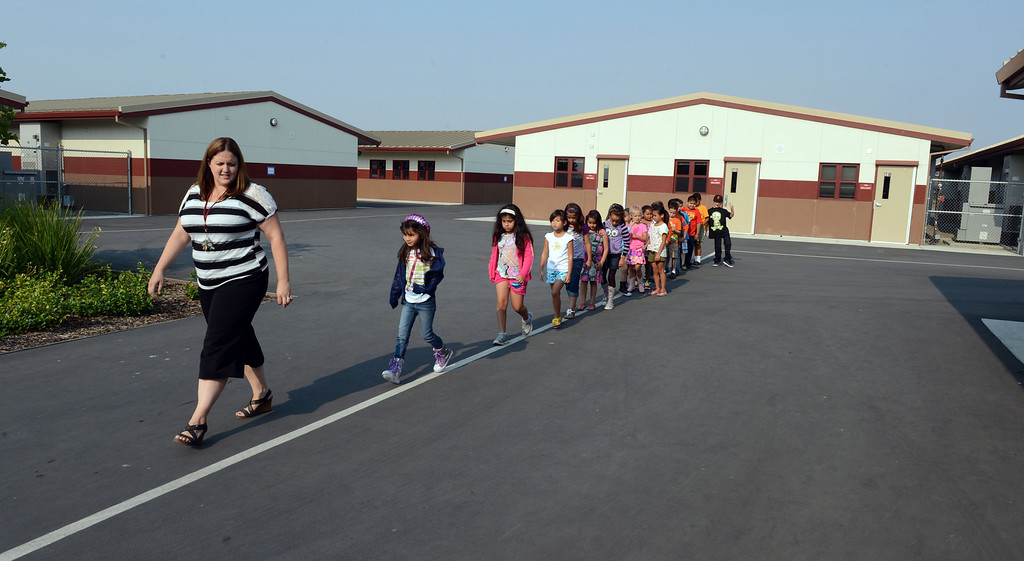 . Second grade teacher Kelly McCoy gives students a tour of their new campus on the first day of school at Mary Casey Black Elementary School in Brentwood, Calif., on Tuesday, July 30, 2013.  McCoy was also telling them the rules about walking along the line when going to the nearby lunchroom.  (Susan Tripp Pollard/Bay Area News Group)