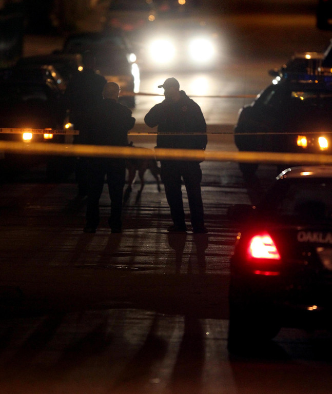 . Oakland police officers investigate the crime scene where a man was gunned down at the corner of 94th Avenue and Hillside Street in Oakland, Calif., on Friday, Jan. 11, 2013.  (Ray Chavez/Staff)