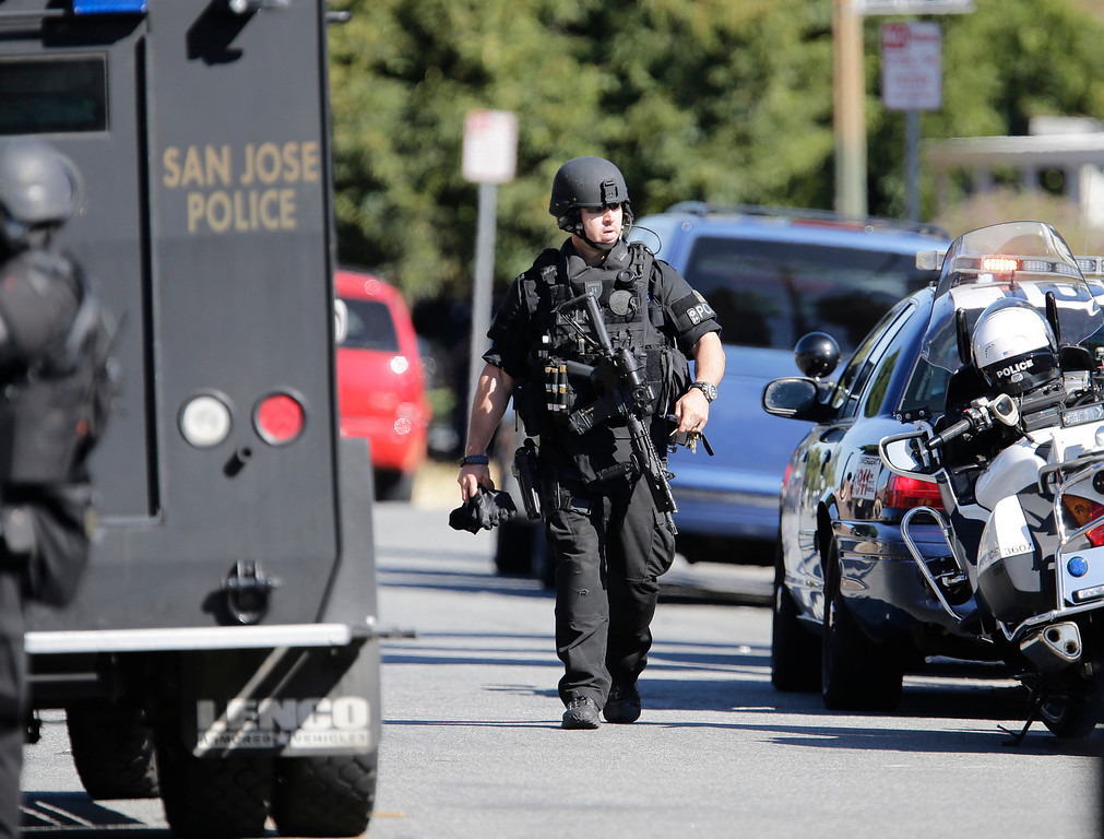 . A member of the San Jose Police Depart MERGE unit prepare to search the neighborhood at Diana Lane and Story Rd. for a gunman who tried to rob a check-cashing store in East San Jose, Calif. on Thursday, Aug. 1, 2013.  (Gary Reyes/Bay Area News Group)