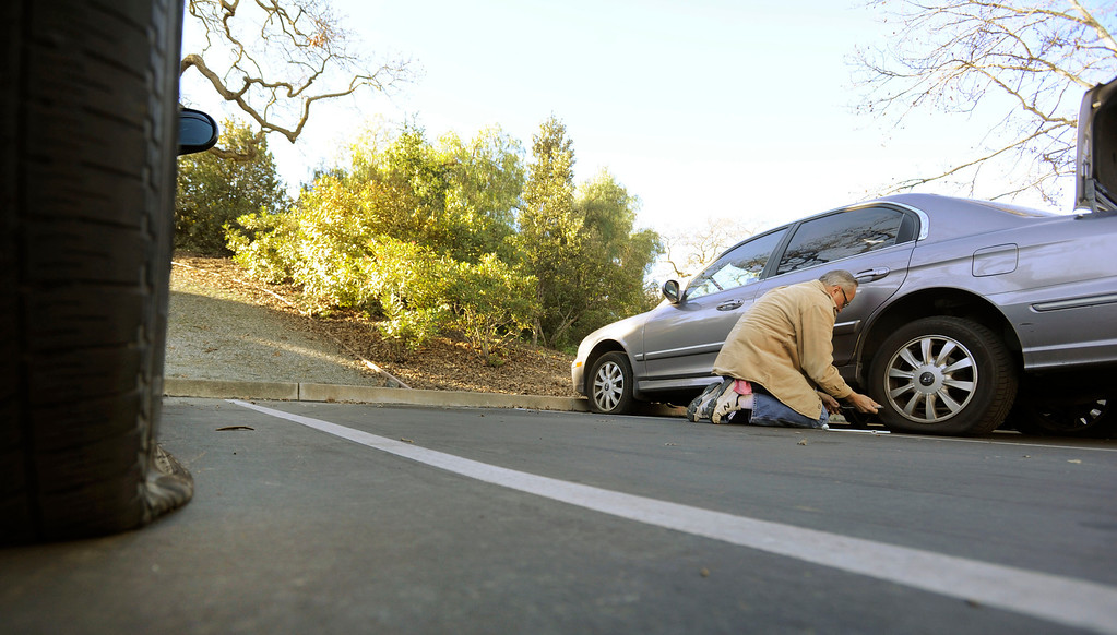 . Dan Zywicki of Concord works on removing the first of four flat tires on his daughter\'s car along Bel Air Drive in Concord, Calif., on Monday, Feb. 11, 2013. Zywicki said his daughter, Kay Zywicki, discovered the flats on Sunday. Concord police reported that tiresd were slashed on about 60 vehicles in the area. (Susan Tripp Pollard/Staff)