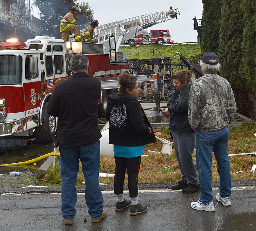 . Neighbors that were affected by a two-alarm fire that happened around 2:26 a.m. on Taylor Road in Bethel Island, look on as firefighters work on cleanup  in Bethel Island, Calif., on Wednesday, March 20, 2013. The blaze destroyed two homes and damaged a third. (Dan Rosenstrauch/Staff)