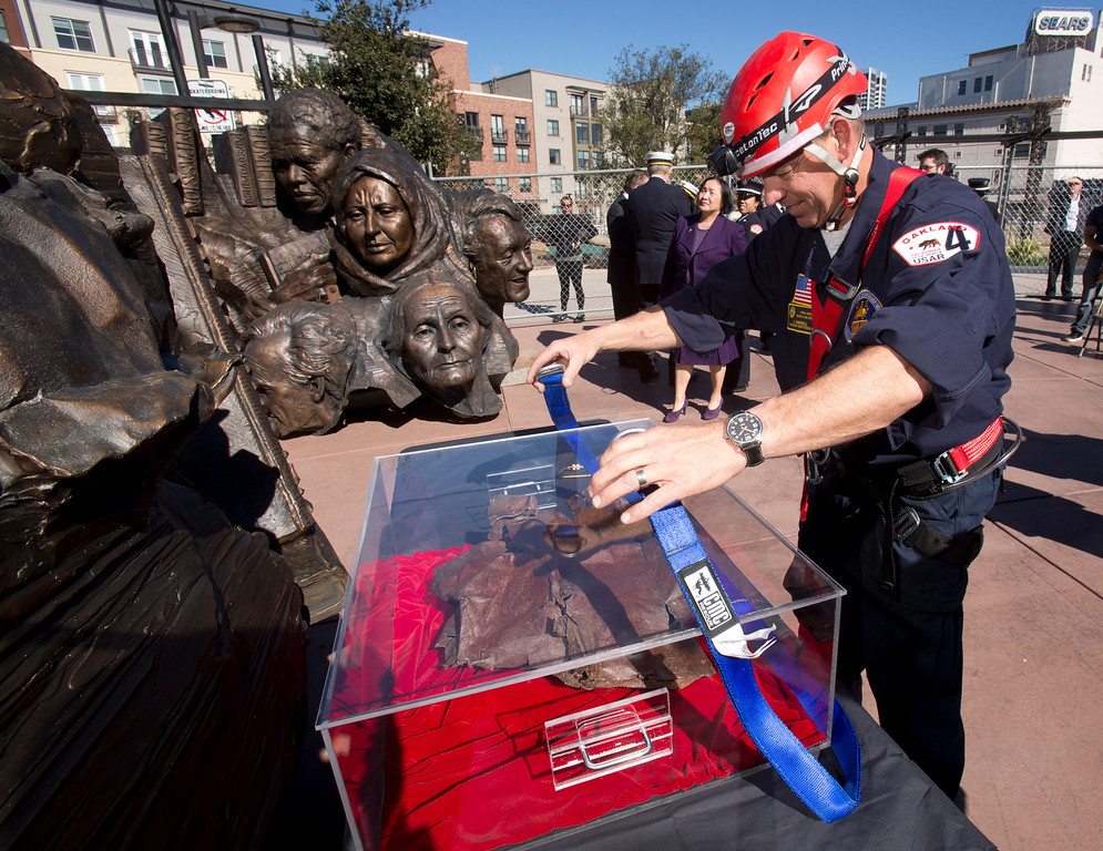 ". John Farrell, an urban search and rescue specialist for the Oakland Fire Department, attaches a strap to a lucite box containing a piece of steel from the twin towers of the World Trade Center, at a ceremony to dedicate the final section of ""Remember Them,\"" artist Mario Chiodo\'s paean to heroes of civil rights and humanity, Thursday, Feb. 21, 2013 in Oakland Calif. Farrell was a member of the search and rescue team from northern California that helped with recovery efforts following the 9/11 attacks. (D. Ross Cameron/Staff)"