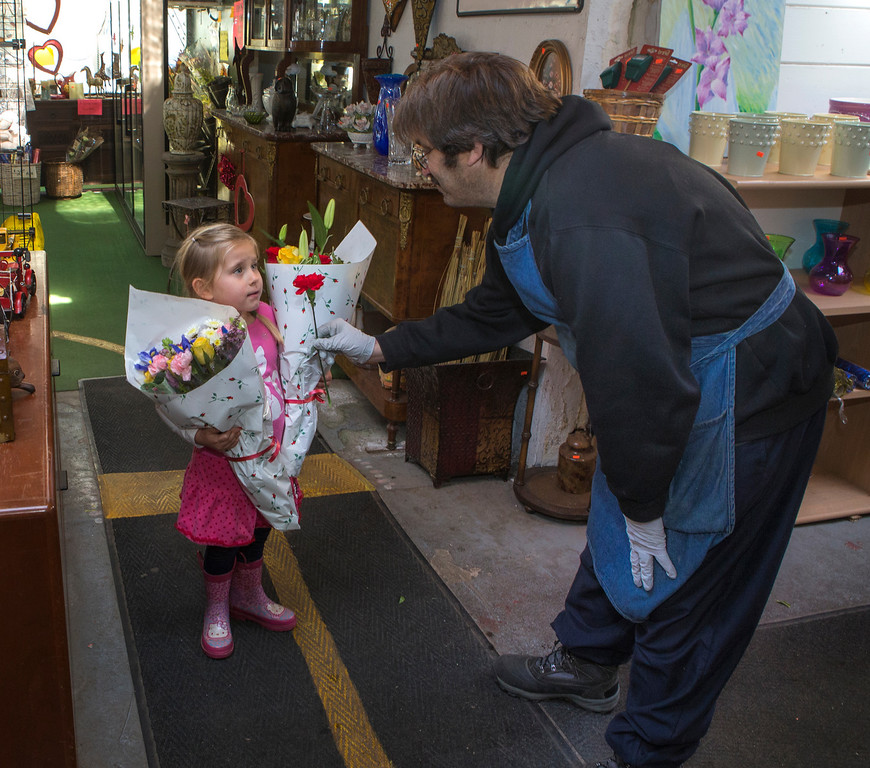 . George Bibbes gives four-year old Violet Holtz a flower at Repetto\'s Greenhouse Florist and  in Half Moon Bay, Calif. on Wednesday, Feb. 13, 2013.