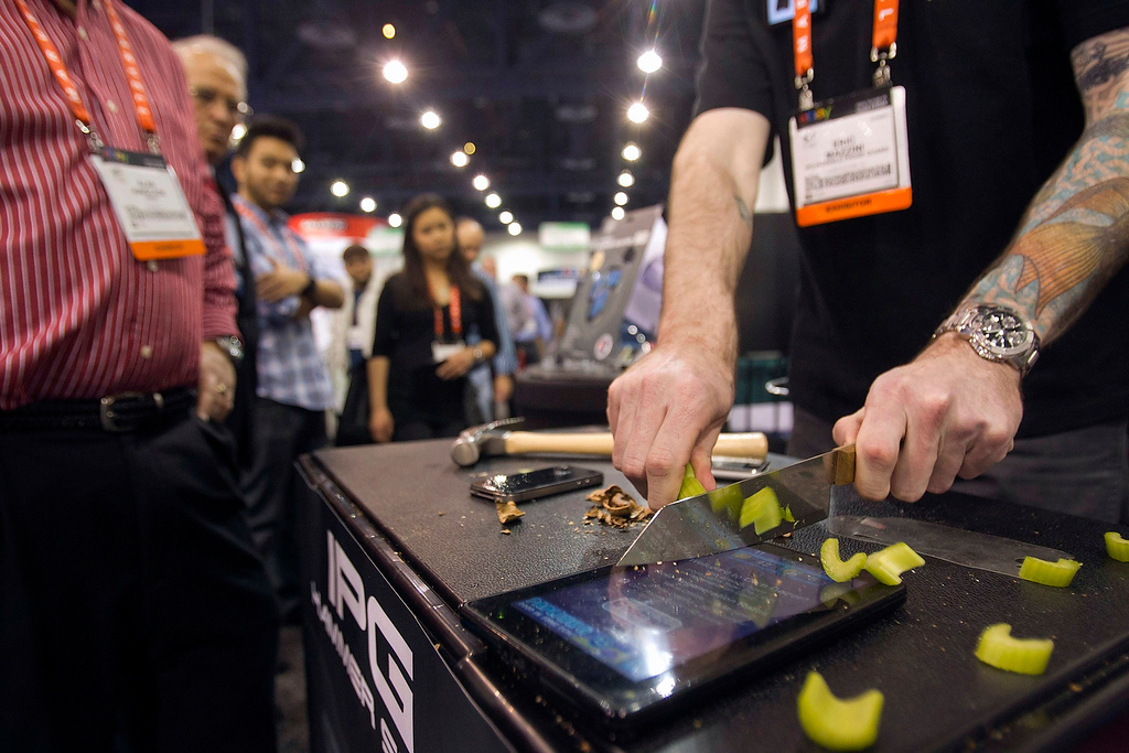 . Eric Mazzini slices celery on top of a Kindle protected with an Invisible Phone Guard (IPG) covering during the first day of the Consumer Electronics Show (CES) in Las Vegas January 8, 2013. The company makes the scratch-proof, self-healing protective covers for over 600 devices. Prices range from $12.95 to $24.95 depending on the model. (REUTERS/Steve Marcus)