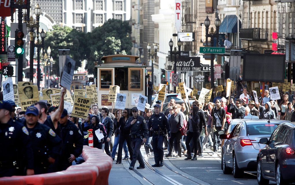. With a police escort, a group marches peacefully up Powell Street in San Francisco, Calif., Sunday afternoon, July 14, 2013 protesting George Zimmerman\'s acquittal Saturday in a Florida courtroom. The march continued to Union Square before heading down Market Street to the Ferry Building. (Karl Mondon/Bay Area News Group)
