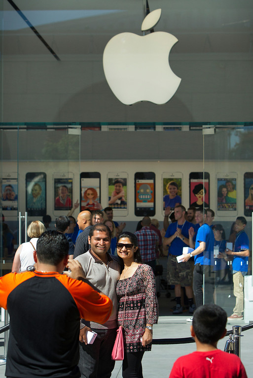 . Pranav and Vishruti Patel, center, are photographed in front of the redesigned Apple Store at the Stanford Shopping Center in Palo Alto, Calif., on Saturday, Sept. 7, 2013.  (LiPo Ching/Bay Area News Group)