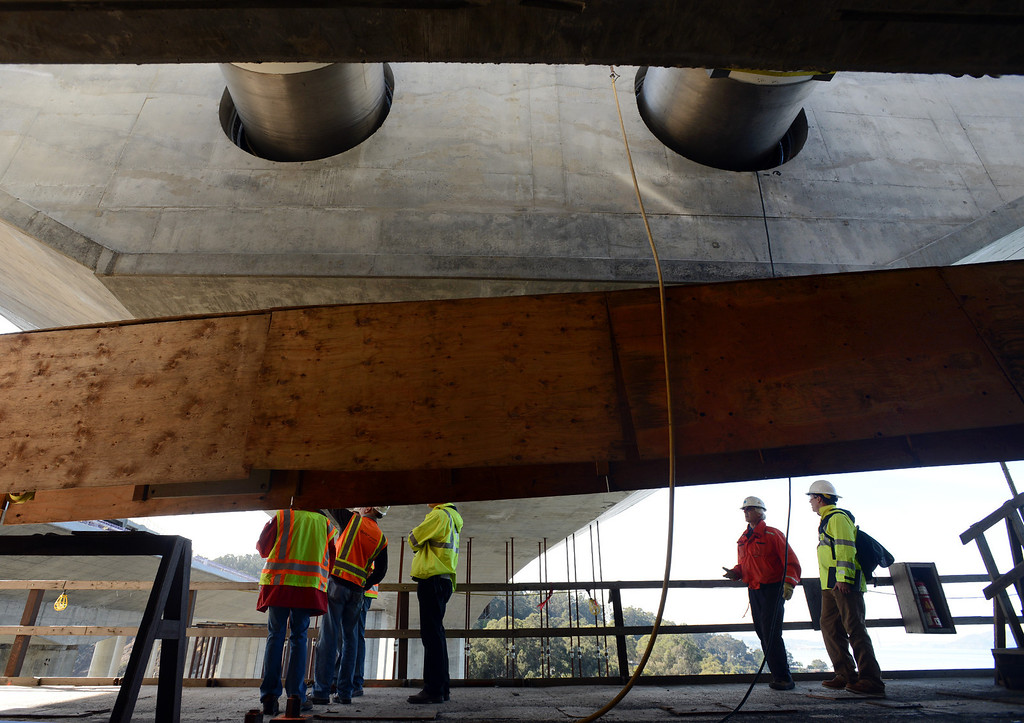 . Covered hinge-pipe beams, two of the 20 installed on the new Bay Bridge, are visible above construction site visitors in November 2012. The hardware acts as a sort of fuse in the event of a large earthquake. The 2,000-pound, 60-foot-long steel pipes fit beneath the roadway and between the bridge segments and can be repaired or replaced if damaged during an earthquake. (Karl Mondon/Bay Area News Group)