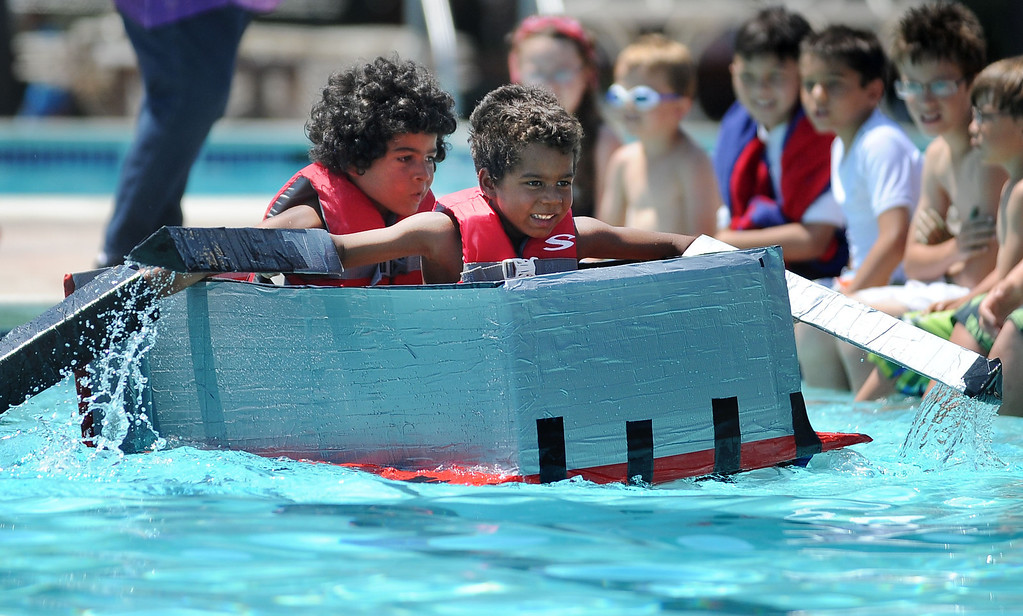 . Ollie Obinyan, left, and his brother Nolan Obinyan, of Pinole, paddle across a pool in their watercraft made of only cardboard, recyclables and duct tape during the Derby Day boat race held at Pleasant Hill Aquatic Park in Pleasant Hill, Calif., on Friday, July 19, 2013. (Doug Duran/Bay Area News Group)