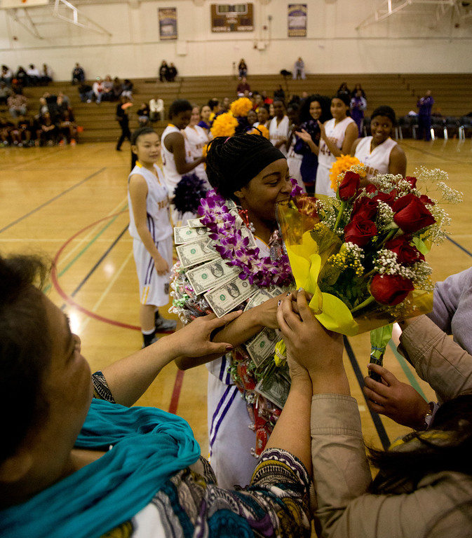 . Oakland Technical High School\'s London Robinson, center, receives flowers and other gifts during a halftime ceremony honoring the team\'s seniors, at an Oakland Athletic League girls\' basketball game, Wednesday, Feb. 20, 2013 in Oakland, Calif. McClymonds won, 62-50. (D. Ross Cameron/Staff)