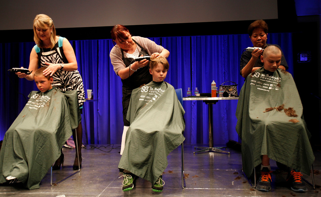 . From left to right, seated, Brady Pernot, 8, Jackson McKinney, 8, and Riley Breier, 11, have their head shaved by volunteers for the St. Baldrick\'s Day head shaving event in support of research for pediatric cancer sponsored by the St. Baldrick\'s Foundation in the NetApp gymnasium at NetApp in Sunnyvale, Calif., on Thursday, March 14, 2013.  (Nhat V. Meyer/Staff)