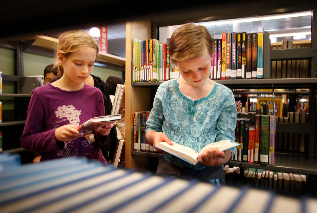 . Sukie Kevane, 10, left, and her friend, Elle Nilson, 12, both of San Jose, look over books on opening day of the new Bascom Branch Library in San Jose Saurday, Feb. 23, 2013.  The 20,000 sq. ft. library features a living room with a fireplace,Tech Center, Group Study Rooms, a large Quiet Study Room, Teen Room, and a Family Learning Center. Public art at the library features artwork by artist Ron Baron titled �Stratigraphy.�  This is one of the four libraries that were delayed opening because of budget problems.  (Patrick Tehan/Staff)