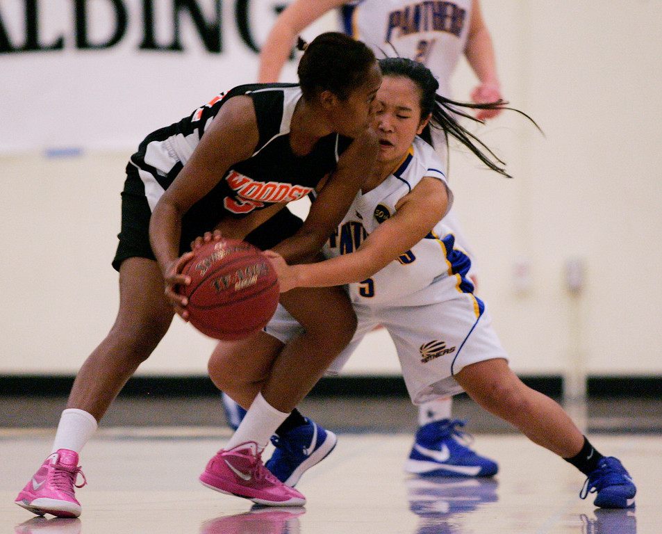 . Presentation\'s Ashley MacDonald tries to steal the ball from Woodsides\'s Sharnon Lionel in the third quarter during the CCS Division II girls basketball finals at Santa Clara High School in Santa Clara, Calif. on Friday, March 1, 2013. The Presentation Panthers beat the Woodside Wildcats, 49-34. (Jim Gensheimer/Staff)