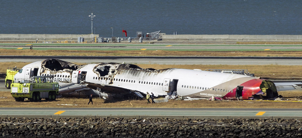 . Firemen and investigators examine the wreckage from a Boeing 777 airplane that crashed while landing at San Francisco International Airport July 6, 2013 in San Francisco, California. An Asiana Airlines passenger aircraft coming from Seoul, South Korea crashed while landing. Two fatalities have so far been reported. (Photo by Kimberly White/Getty Images)