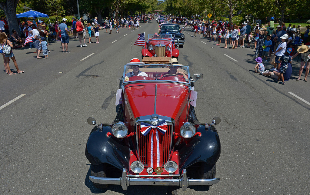 . Andy Moyce, of Oakland, and his wife Mary, drive their 1952 MGTD during Piedmont\'s July 4th parade in Piedmont, Calif., on Thursday, July 4, 2013. (Jose Carlos Fajardo/Bay Area News Group)