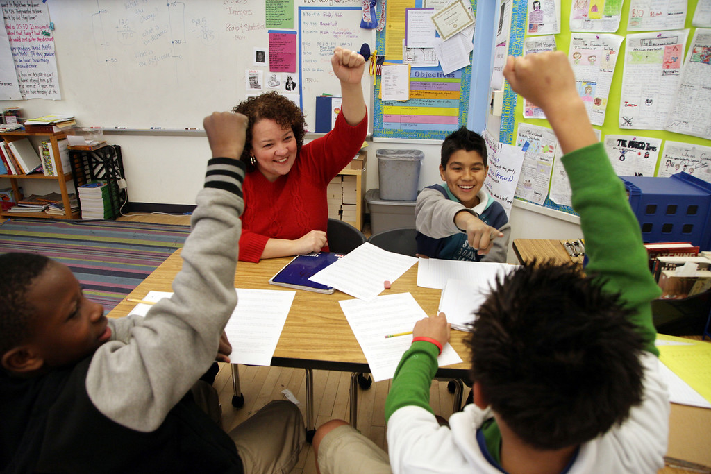 . Teacher Stephanie Perry works with students Ruben Molina, 11, right, Amari Blackwell, 12, left, and Marco Baca, 12, front, on some 6th grade math word problems during class at Peres Elementary School in Richmond, Calif., on Friday, Feb. 8, 2013.  Peres school is one of two elementary schools in Richmond that have raised their average API test scores to over 800. (Laura A. Oda/Staff)