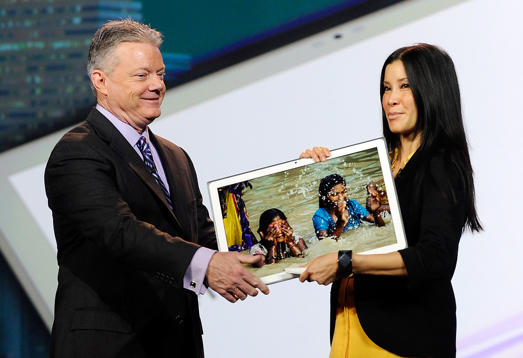 . Panasonic North America CEO Joe Taylor (L) hands off Panasonic\'s new 4K 20 inch tablet to host Lisa Ling during a keynote address at the 2013 International CES at The Venetian on January 8, 2013 in Las Vegas, Nevada. (Photo by David Becker/Getty Images)