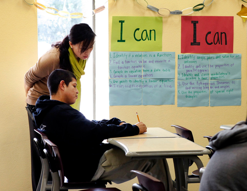 . Acting principal Jamy Cho checks the work of a freshman student during an algebra class at ACE Charter High School in San Jose, Calif. on Wednesday, Dec. 05, 2012.  (Karl Mondon/Staff)