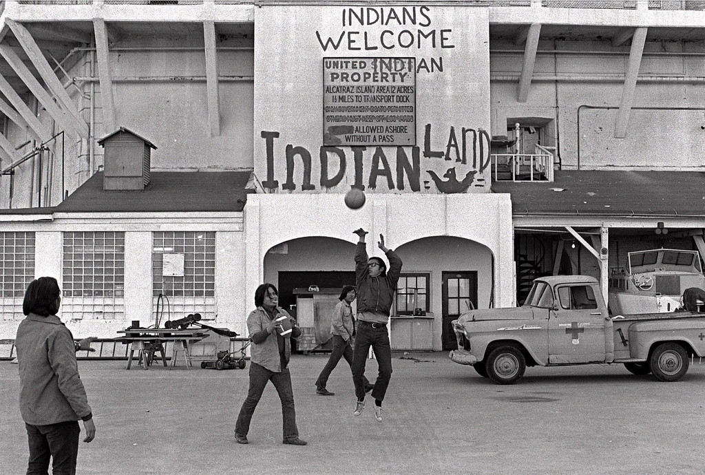". American Indians play ball games outside the prison wall on Alcatraz Island in San Francisco during their occupation of the island in this Nov. 26, 1969 file photo. The sign reading ""INDIANS WELCOME,\"" is one of the few physical reminders that 30 years ago a group of American Indians clung to the barren, bony slopes of Alcatraz for 19 months, winning the attention of the world and igniting a passion for civil rights. (AP Photo/File)"