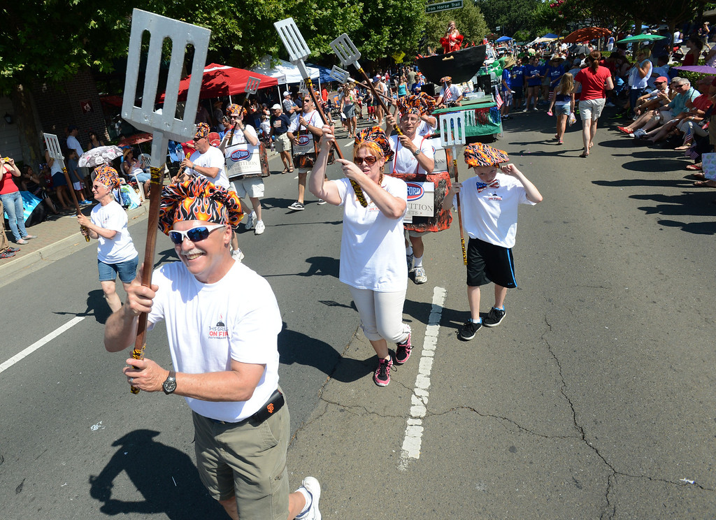 """. San Ramon Valley United Methodist Church Senior Pastor Ron Dunn, and other embers of the \""""Holy Smokes\"""" Grill Team take part in the 4th of July Parade in Danville, Calif., on Thursday, July 4, 2013. The parade, sponsored by the Kiwanis Club of San Ramon Valley, features about 120 entries with an estimated 40,000 spectators attending. (Doug Duran/Bay Area News Group)"""