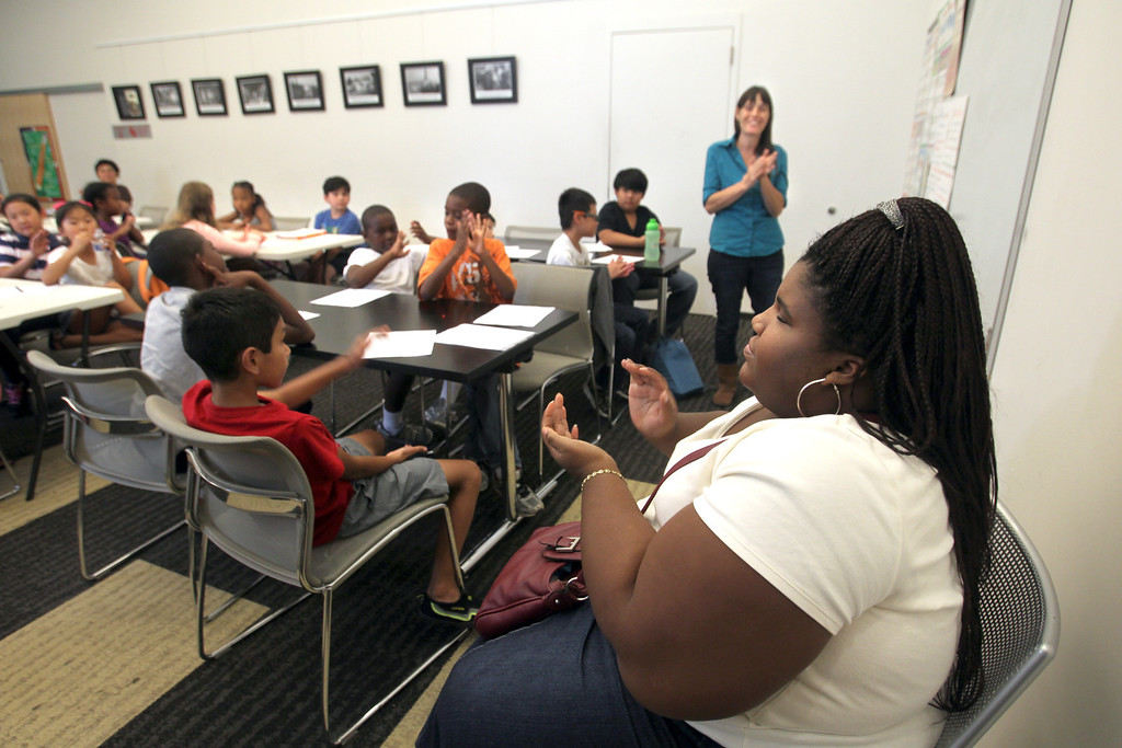 . Camille Winfield, right, of Hercules High School, claps her hands along with children after singing during the Wild About Writing class taught by Sarah Creeley, far right, at Hercules Public Library in Hercules, Calif., on Wednesday, July 24, 2013. (Ray Chavez/Bay Area News Group)