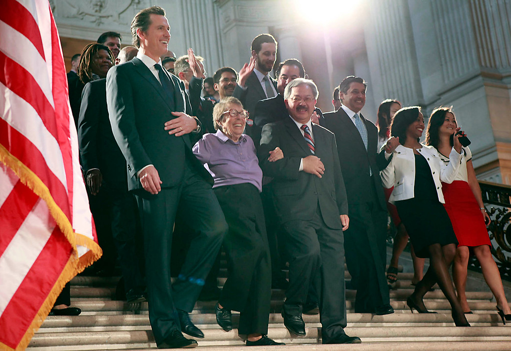 . Lt. Gov. Gavin Newsom and San Francisco Mayor Ed Lee walk Phyllis Lyon down the steps of the San Francisco City Hall rotunda to a cheering crowd after the Supreme Court overturned Proposition 8 Wednesday morning, June 26, 2013 in San Francisco, Calif. Phyllis Lyon was married to her longtime partner Del Martin in City Hall in 2005. (Karl Mondon/Bay Area News Group)