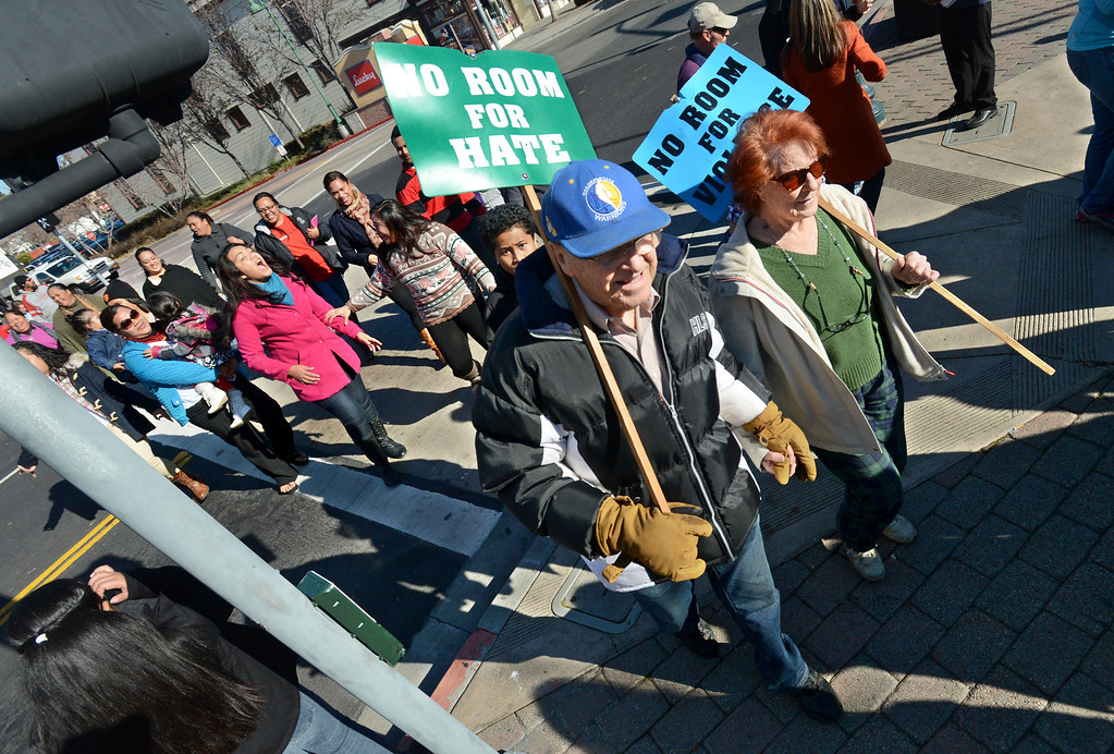 . Byron Schatz, left, and Alison Corson, both of Hayward, carry signs during the 10th annual interfaith Martin Luther King Jr. Day march and rally in Hayward, Calif., on Monday, Jan. 21, 2013. The rally, held at the Hayward City Hall Plaza, featured words of King and music from the First United Methodist Church of Hayward, the First Tongan United Methodist of San Bruno and Congregation Shir Ami of Castro Valley.  (Doug Duran/Staff)