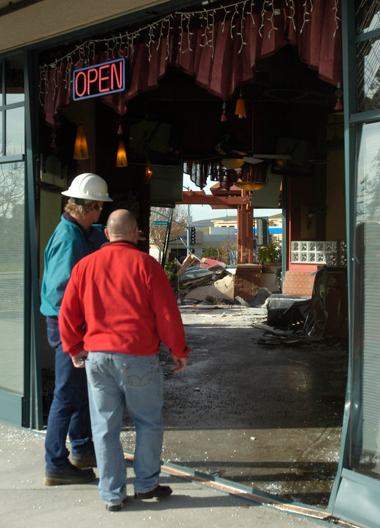 . Jim Coates, right, who was involved in a recent remodel of the Strings Italian Cafe and happened to be eating lunch here with several other people today, surveys damage left behind by a Cadillac Escalade SUV driven by accident through the restaurant during the lunch hour in Livermore, Calif., on Monday, Jan. 7, 2013. One customer was taken to a hospital for treatment of injuries and several other people sustained minor injuries. (Cindi Christie/Staff)