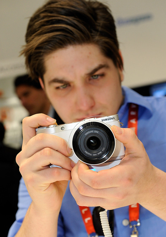 . Attendee Andrew Regna examines the Samsung NX300 digital camera at the 2013 International CES at the Las Vegas Convention Center on January 8, 2013 in Las Vegas, Nevada. (Photo by David Becker/Getty Images)