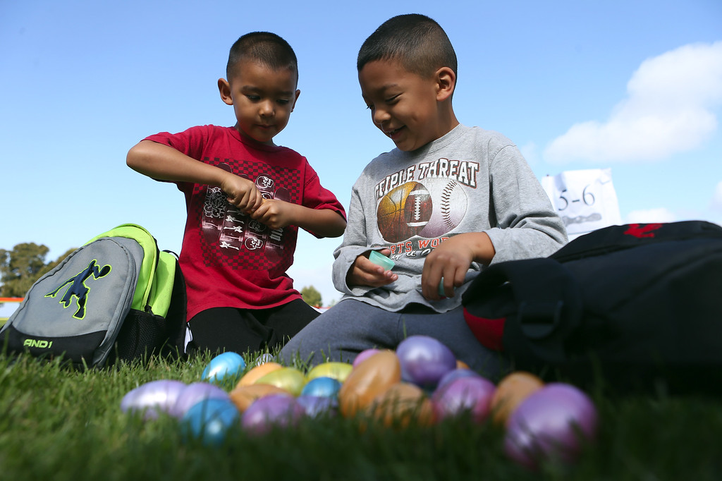 . Brothers Brandon, 5, and Joshua, 7, Hong, from left, of San Leandro, crack open plastic Easter eggs at the annual San Leandro Easter egg hunt held at Marina Park in San Leandro, Calif., Saturday, April 12, 2014. The event has been held every year since 1951 and this year is sponsored by the San Leandro Optimist Club. 8,000 eggs with a candy or sticker surprise were given away. (Anda Chu/Bay Area News Group)