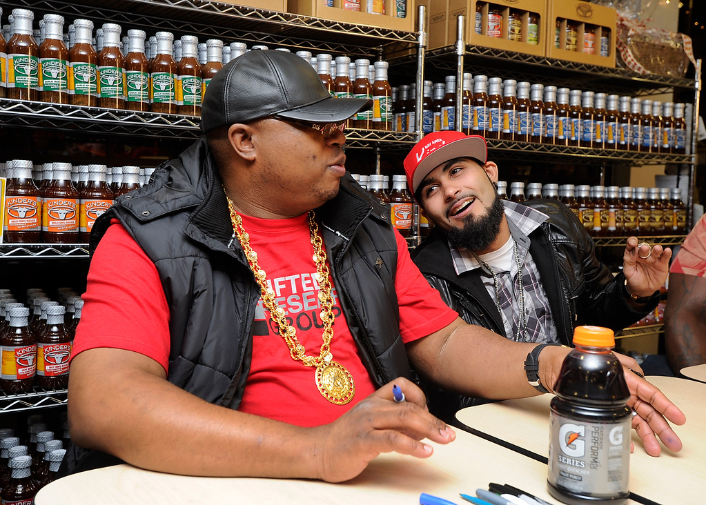 . Rapper E-40, who grew up in Vallejo, and Giants reliever Sergio Romo appear at a Kinder\'s Meats and Deli on Wednesday, Dec. 12,  2012, in Pleasant Hill, Calif. The two teamed up to support Marine Corps Reserve Toys For Tots by signing autographs for fans who brought in a toy to support the program. (Susan Tripp Pollard/Staff)