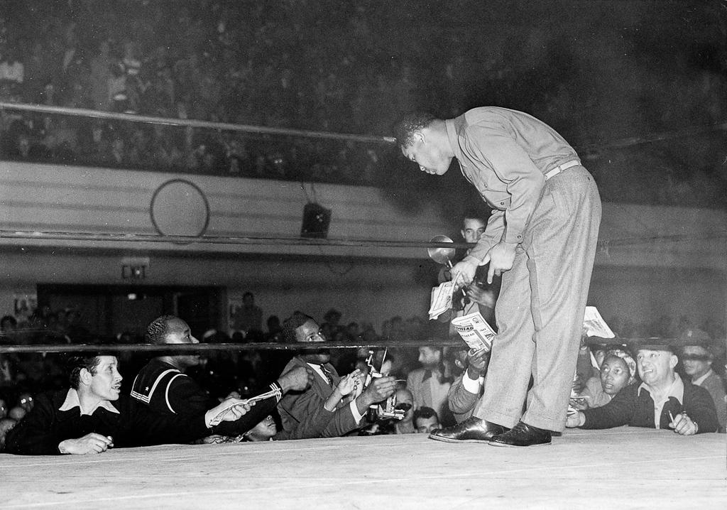 . Oakland, CA October 31, 1945 - Joe Louis signs autographs between rounds at the Oakland Auditorium. Louis refereed the semi-windup on the Harold Blackshear, Abel Cestac card. (Oakland Tribune Photo)