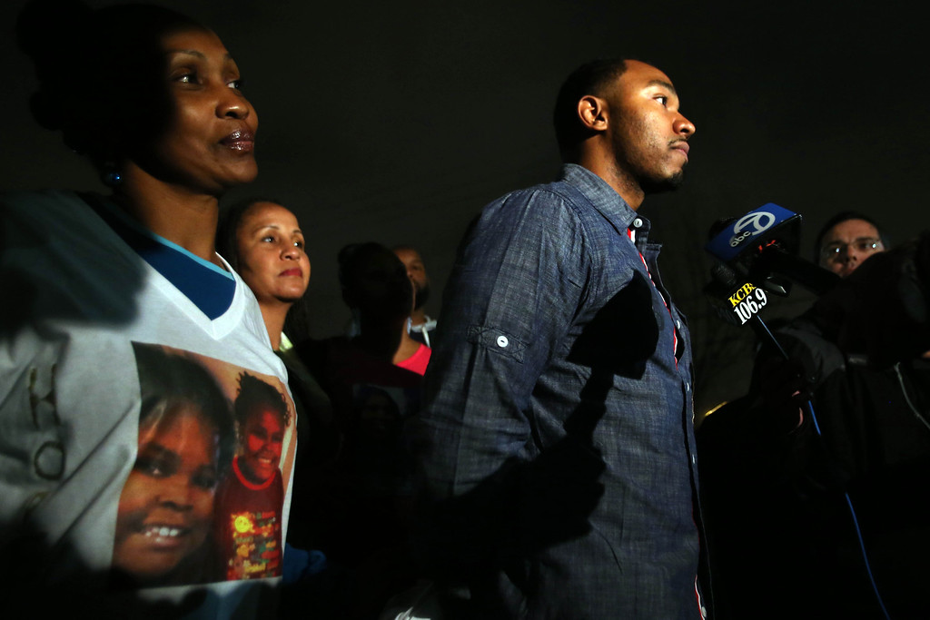. Omari Sealey, right, uncle of 13-year-old Jahi McMath, speaks to the media after the family held a prayer vigil for the girl at Paradise Baptist Church in Oakland, Calif., on Wednesday, Dec. 18, 2013. Jahi went into Children\'s Hospital Oakland to have a three-part surgery to remove her tonsils and clear tissue from her nose and throat to treat her sleep apnea and is now brain dead. Family asked for a one-hour prayer vigil for the girl internationally from 6 to 7 p.m.  (Ray Chavez/Bay Area News Group)