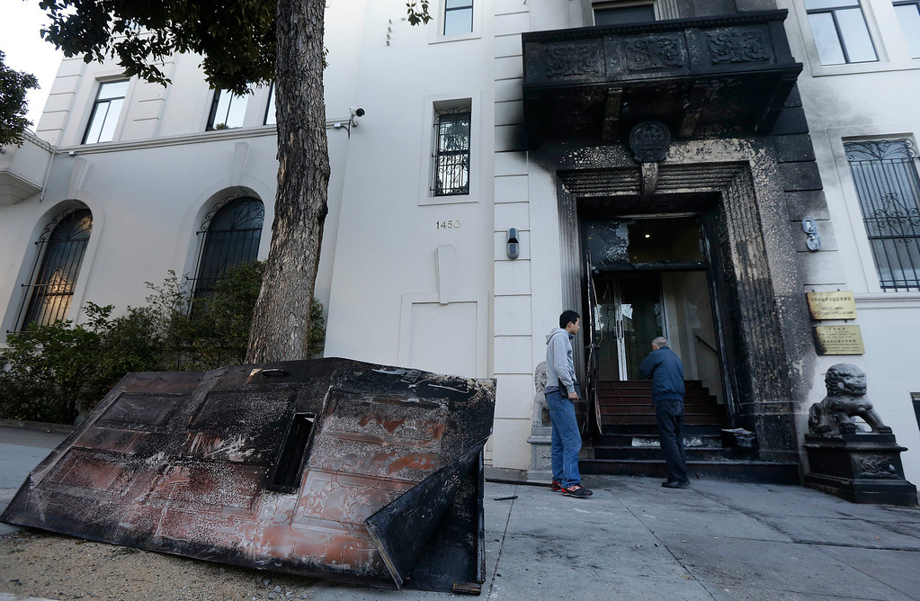 . Two men look at the damage to the entrance of the Chinese Consulate in San Francisco on Thursday, Jan. 2, 2014. The consulate said in a notice on its website that a person came out of a van parked outside the compound Wednesday night with two buckets of gasoline, poured the fuel on the front of the consulate building and set it on fire. (AP Photo/Jeff Chiu)