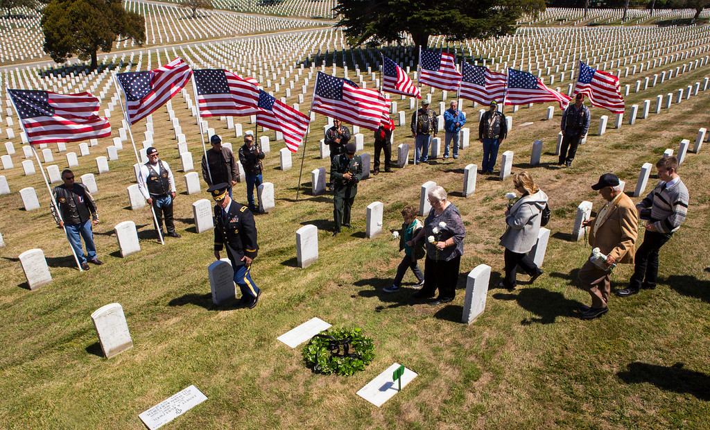 . Marlene Baisa, middle, the niece of Sgt. 1st Class Joseph Steinberg carries flowers to lay at the gravesite of her late uncle at Golden Gate National Cemetery in San Bruno, Calif., on Aug. 1, 2013. (John Green/Bay Area News Group)
