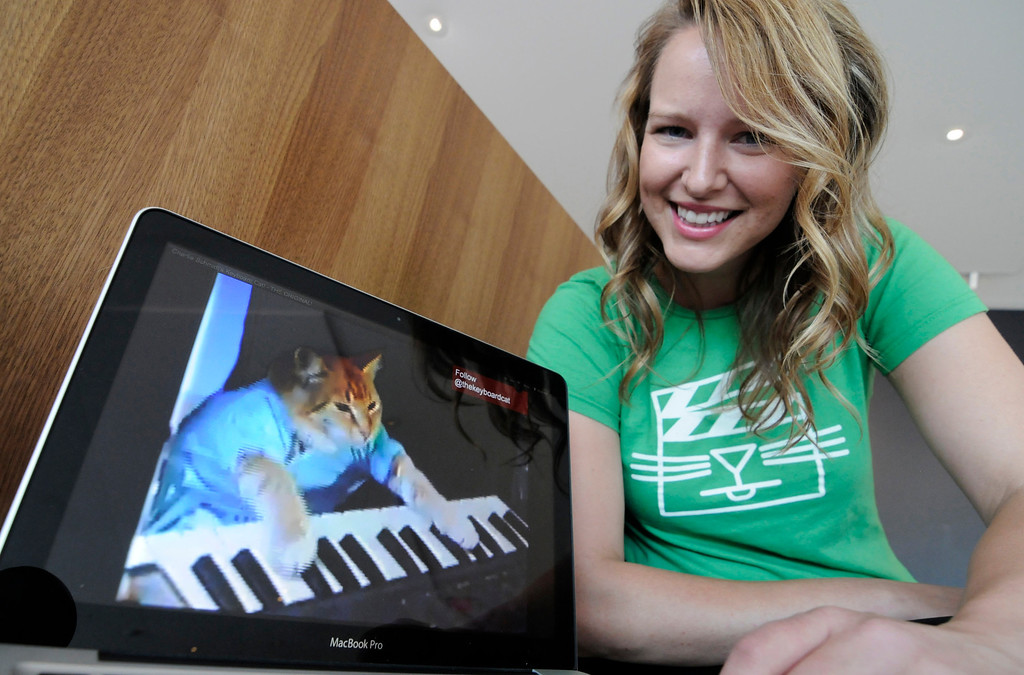 ". FILE - In this Wed., Aug. 29, 2012 file photo, Katie Hill, a program associate with the Walker Art Center, shows a frame from a cat video of a cat playing the piano, in Minneapolis. The Walker presented its  first ""Internet Cat Video Film Festival\"" to showcase the best in filmed feline hijinks that drew a crowd of more than 10,000 people. 80 videos culled from 10,000 submissions that covered the simple, funny moment to polished animations and kitty works made by trained filmmakers were shown to the public for free. (AP Photo/Jim Mone, File)"