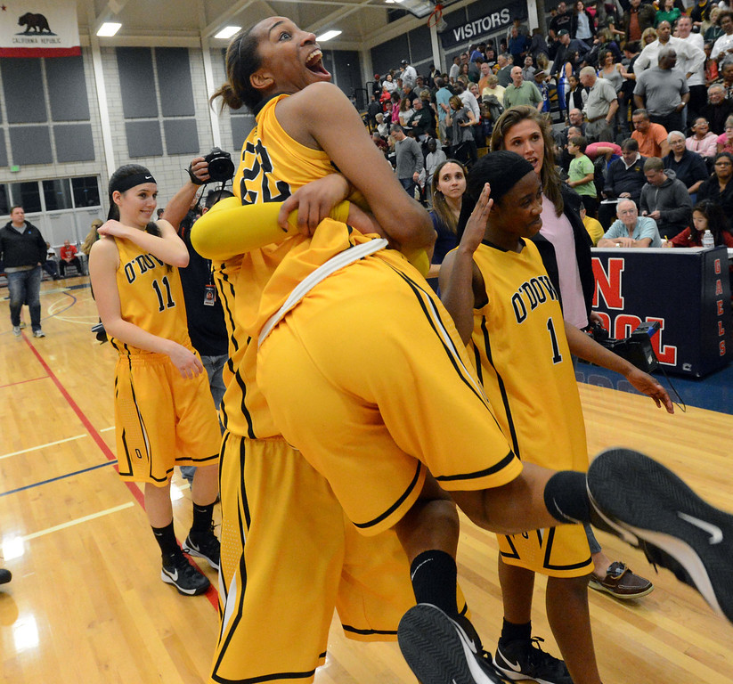 . Bishop O\'Dowd High\'s K.C. Waters (44) picks up teammate  Oderah Chidom (22) after winning their Division III North Coast Section basketball game 77-48 against Miramonte High in Dublin, Calif., on Saturday, March 2, 2013. (Doug Duran/Staff)