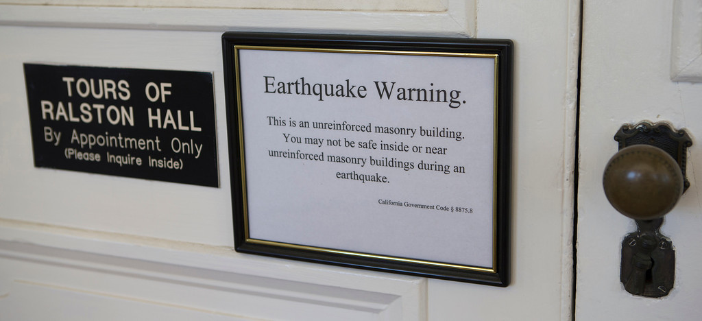 . An earthquake warning sign is posted on the front door of Ralston Hall on the campus of Notre Dame de Namur University in Belmont, Calif., on Wednesday, Feb. 20, 2013. (John Green/Staff)