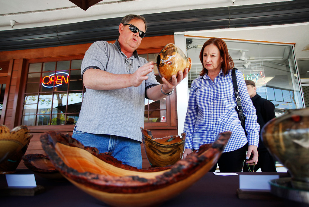 . Artist Jeff Davison, left, talks to Laura Lilyquist, of Menlo Park, about his hand-crafted woodwork at his booth, Wood Turning Obsession, during the 31st annual Sidewalk Fine Arts Festival on Santa Cruz Avenue in downtown Menlo Park on Friday, April 19, 2013. The festival has artworks including painting, jewelry, and sculpture. The festival started Friday and continues to Sunday. The festival is open today, Saturday, from 10 a.m. to 6 p.m. and Sunday from 10 am. to 5 p.m. For more information, visit pacificfinearts.com.  (Kirstina Sangsahachart/ Daily News)