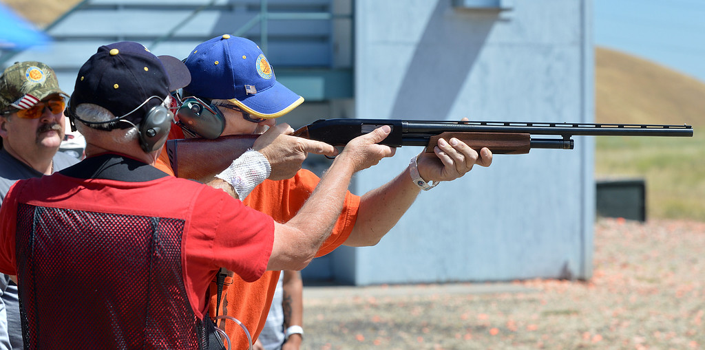 . Coach Frank Thorngurgh, of Concord, left, looks on as John Gilbert, of Sacramento, a Army medic during the Vietnam war, takes a shot at a flying clay target during the George Findly Memorial Disabled Veteran Trap Shoot at the Bay Point Rod and Gun Club in Concord, Calif., on Saturday, June 15, 2013.  Each vet was assigned a mentor/coach from the club and each got to shoot two sets of flying clay targets.  (Dan Rosenstrauch/Bay Area News Group)
