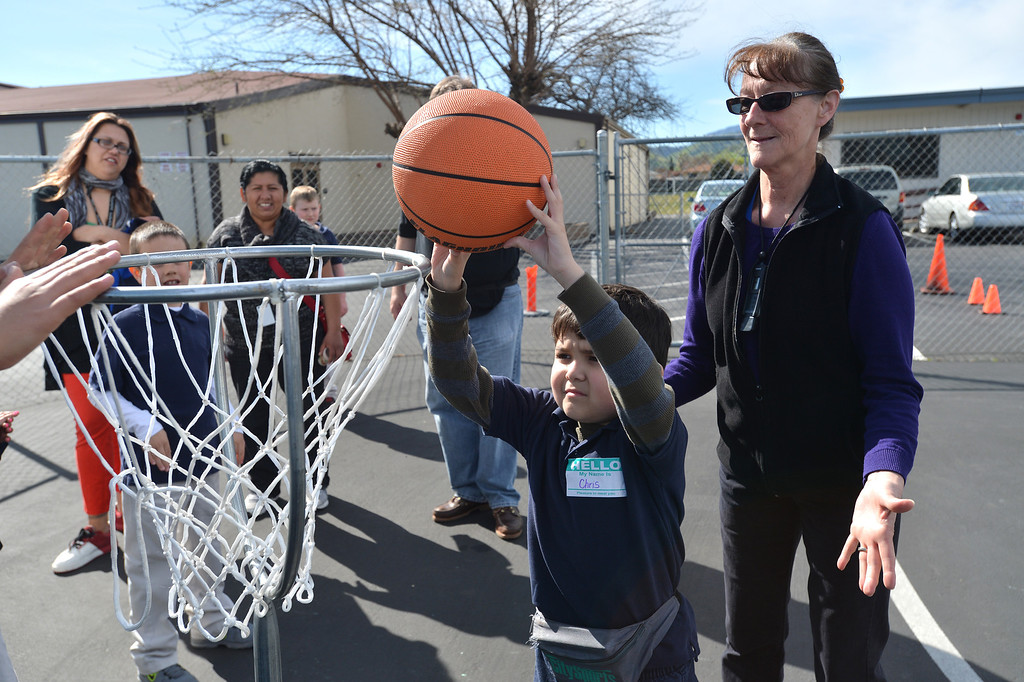 . Iris Yunck, an instructional assistant for the Contra Costa County Office of Education\'s East County Student Programs, watches as Chris, 8, of Antioch shoots the basketball during a Special Olympics basketball skills event at Turner Elementary School in Antioch, Calif., on Friday March 8, 2013.  (Dan Rosenstrauch/Staff)