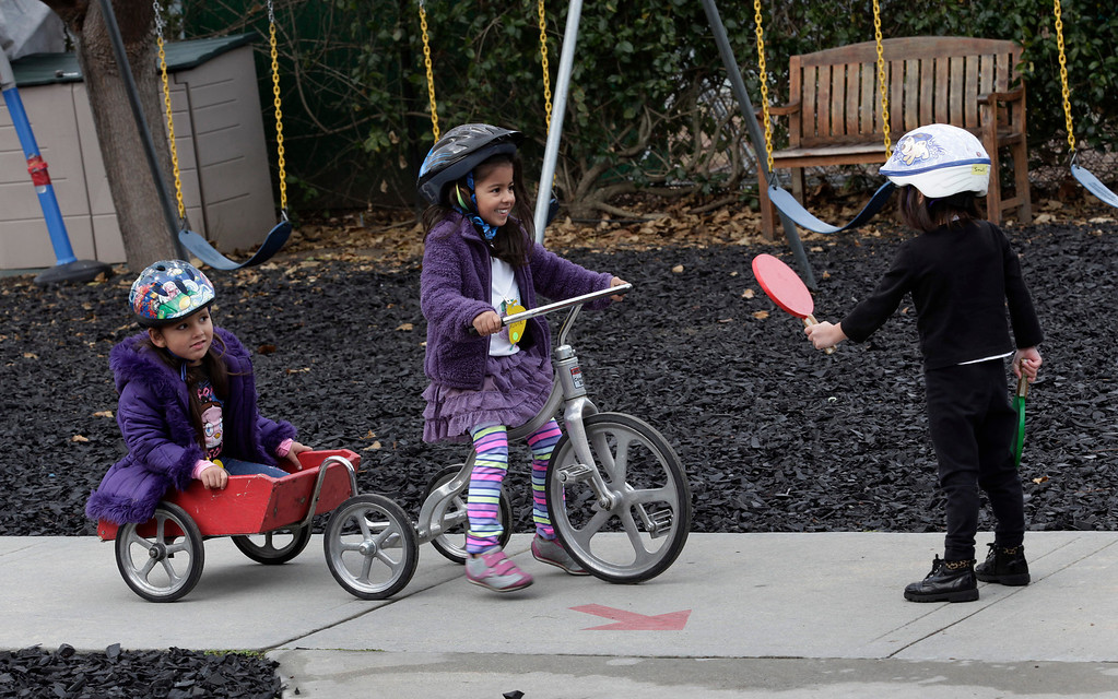. Moni Oseguera, 4, Maddie Dhillon, 4, and Akemi Honma,4, play stop-and-go on the playground at the Mountain View Parent Nursery School in Mountain View, Calif. on Friday, Feb. 8, 2013. The Mountain View-Whisman School District has decided that if parents hold back an eligible child from kindergarten, it will help evaluate those children for kindergarten-readiness the following year. Some will be sent to first grade rather than kindergarten. (Gary Reyes/ Staff)
