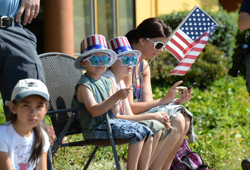 . Cayden Mills, 5  left, Jared Mills, center, and their mother Tina Mills, all of Hayward, watch the Fourth of July parade in Fremont, Calif., on Thursday, July 4, 2013. The parade featured more than 70 entries. (Dan Honda/Bay Area News Group)