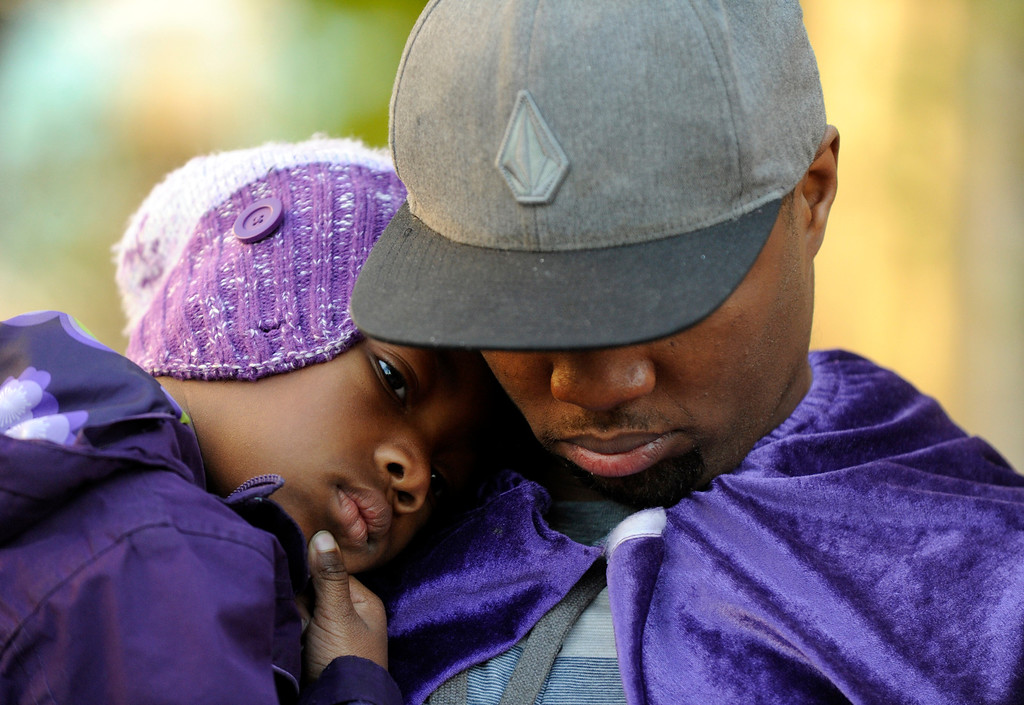 . Quinton Reynolds, of Emeryville, wears a purple cape as he holds his daughter Qniyah Reynolds, 4, as he gathers with others outside of Children\'s Hospital Oakland in support of Jahi McMath in Oakland, Calif., on Monday, Dec. 23, 2013. Reynolds said Jahi\'s story touches everyone and he wanted to be there to help strengthen, heal and show love for the family. Many wore purple Jahi\'s favorite color to show support.  (Susan Tripp Pollard/Bay Area News Group)