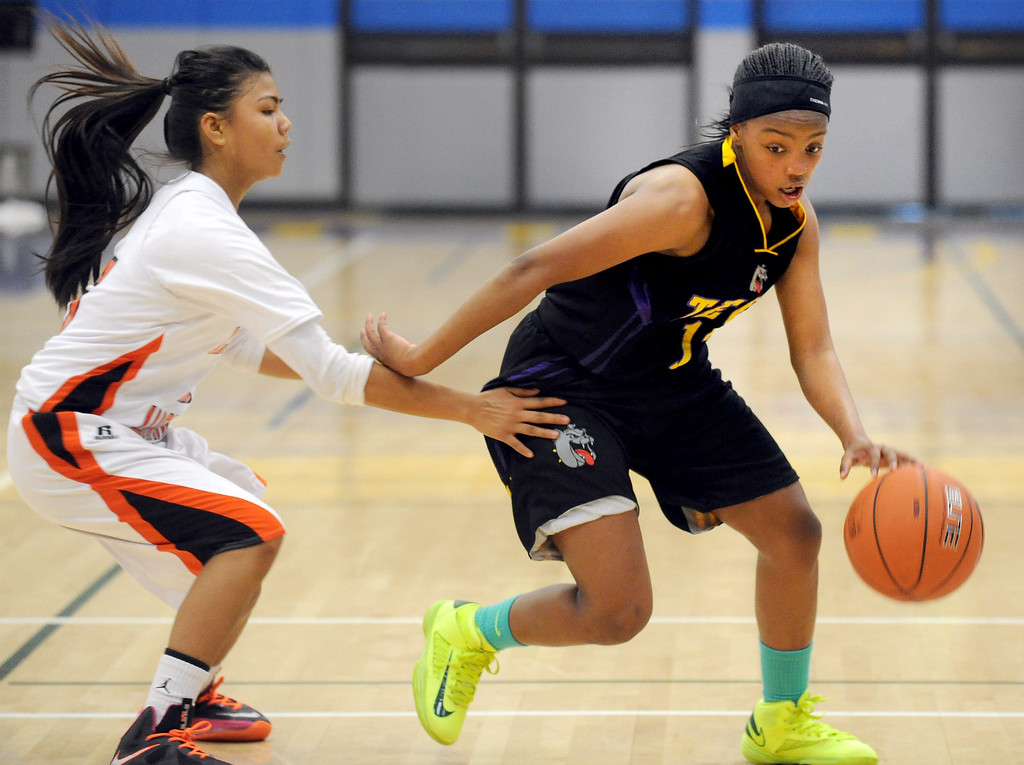 . McClymonds High\'s Romanalyn Inocencio (5) tries to slow down Oakland Tech High\'s Elayshia Woolridge (12) in their Oakland Section high school girls basketball championship game played at Merritt College in Oakland, Calif. on Thursday, Feb. 28, 2013. (Dan Honda/Staff)